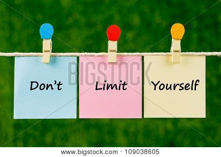 Word Quotes Of Don't Limit Yourself On Sticky Color Papers Hanging On Rope.