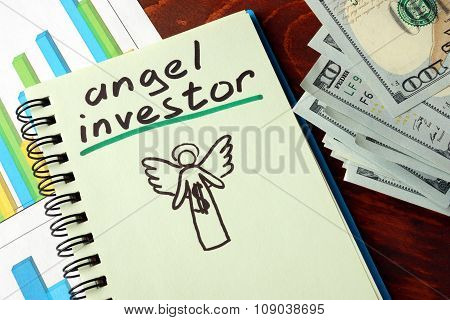 Notebook with angel investors sign on a table.