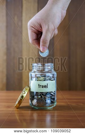 Image Of Hands Putting Coin Into Clear Bottle With Travel Label Against Blurred Wooden Background.