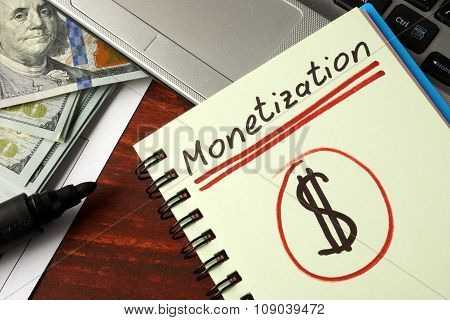 Notebook with monetization sign on a table.