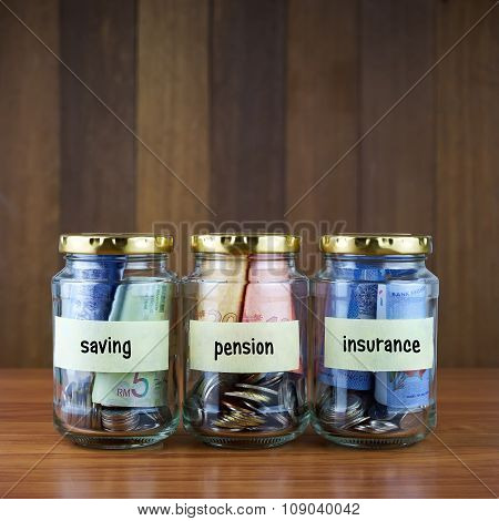 Image Of Money In Clear Bottles With Saving, Pension, Insurance Labels.