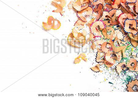 a bunch of multi-colored chips on a pencil sharpener on a white background