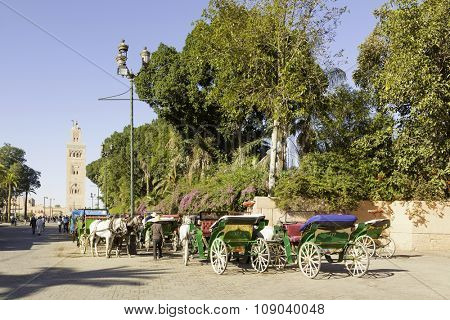 Marrakesh, Morocco - November 7, 2015: Horse-drawn carriages waiting at Djemaa el Fna square. Minaret of Koutoubia mosque in background.
