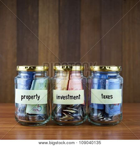 Image Of Money In Clear Bottles With Property, Investment, Taxes Labels.