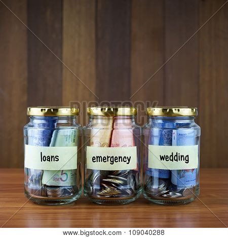 Image Of Money In Clear Bottles With Loans, Emergency, Wedding Labels.