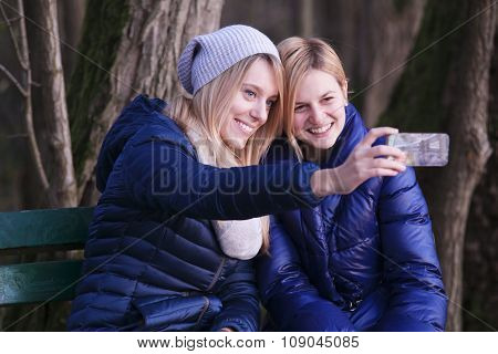 Young woman sitting on bench with her best friend
