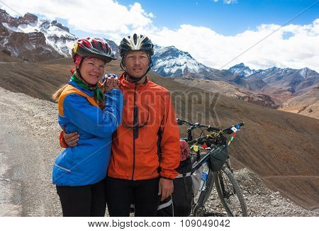 Happy cyclist couple standing on mountains road. Himalayas, Jammu and Kashmir State, North India
