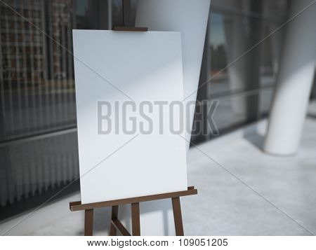 Wooden easel with a blank white canvas near office building.
