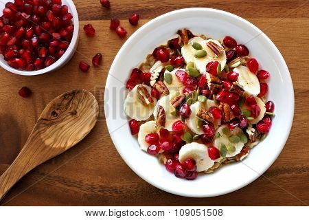 Breakfast oatmeal with pomegranate, bananas, seeds and nuts