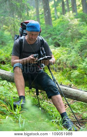 Hiker Man Is Resting And Determines His Position In The Forest With The Help Of Gps-receiver And Map