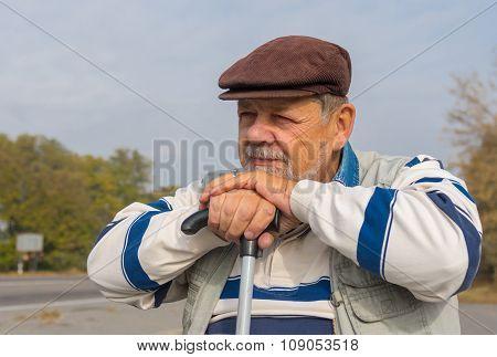 outdoor portrait of senior man with walking stick