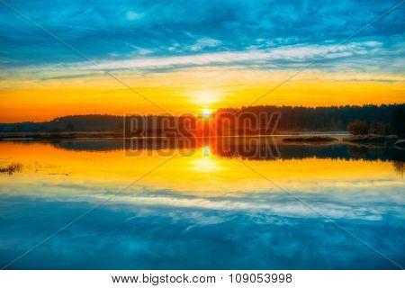 Bright beautiful Sunrise over Calm Lake, River and forest horizo