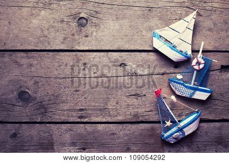 Decorative Sailing Boats On  Aged  Wooden Background.