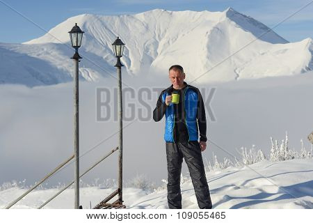 Man Relaxing Standing With Cup Of Coffee On The Background Of Snow-capped mountains