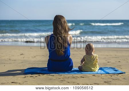 Mother And Baby Sitting On A Beach