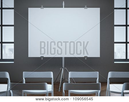 Conference room with blank screen and rows of chairs.