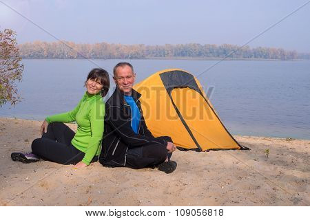 Happy Hiking Couple Rests In The Camp On The River Bank In A Beautiful Autumn Day