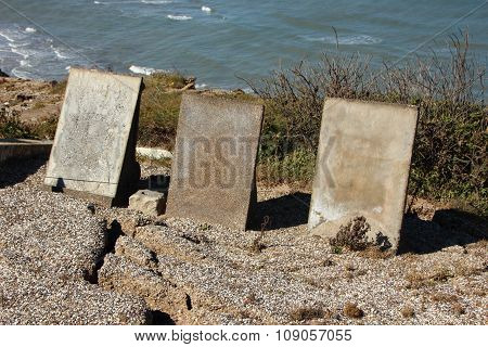 Three Headstone At Edge Of Cliff With Ocean Background