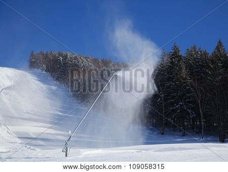 Scenic View Of Ski Slope With Snow Guns Operating