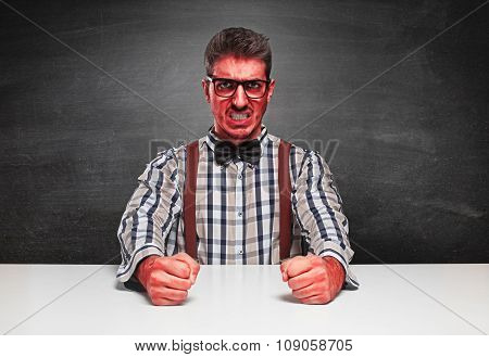 Angry genius furious on blackboard background