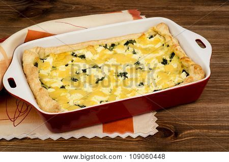 Quiche with spinach, feta and cheese - traditional dish of french cuisine.