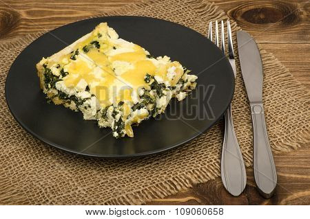 A piece of quiche with spinach, feta and cheese - traditional dish of french cuisine