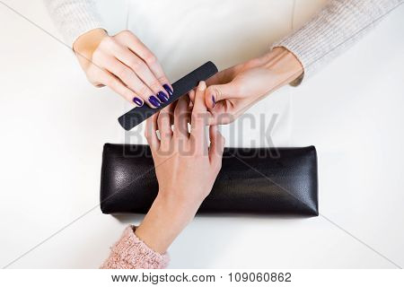 Manicurist polishing index finger for manicure