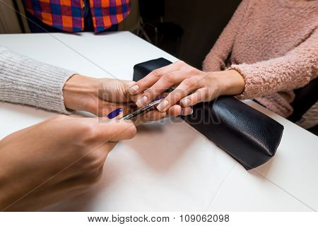 Manicurist make manicure client in nail salon