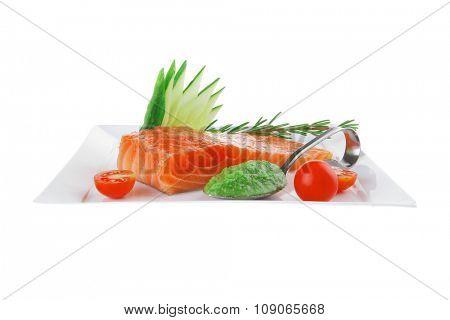 smoked salmon bar on plate with tomatoes and pesto sauce