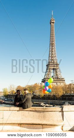 The Couple Of Men With Balloons And Eiffel Tower In The Background.