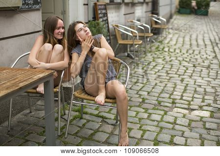 Young girls gossiping while sitting in a street cafe.