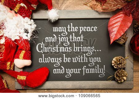 Blackboard with the text: May the Peace and Joy That Christmas Brings... Always Be With You And Your Family