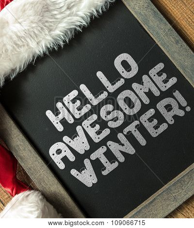 Hello Awesome Winter written on blackboard with santa hat