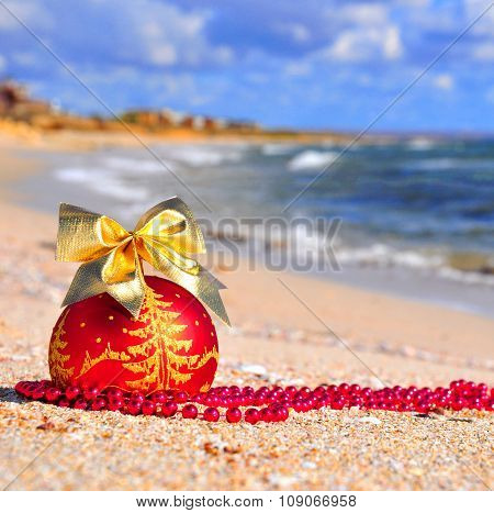 Red Christmas Ball With Golden Bow On The Sand