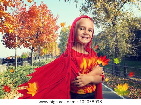 Little girl in masquerade costume in an autumn street