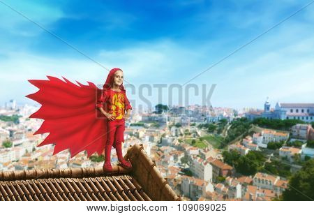 Little girl in a superhero costume standing on the roof against cityscape
