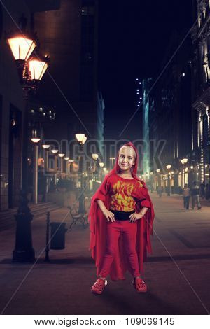 Little girl in masquerade costume in the evening street