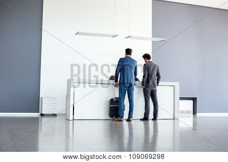 Young businessmen check in at airport reception