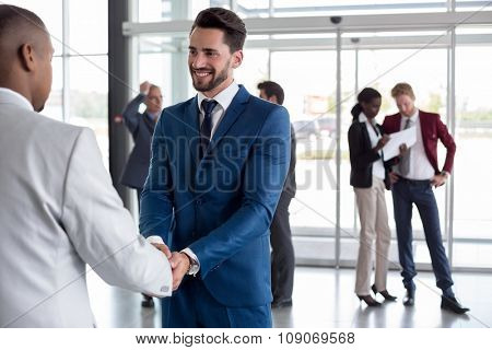 Handsome man at entrance heartily welcome black man