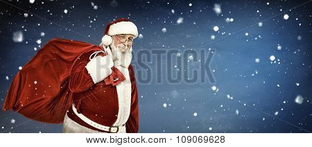 Santa Claus carrying  a bag full of gifts, on copyspace background