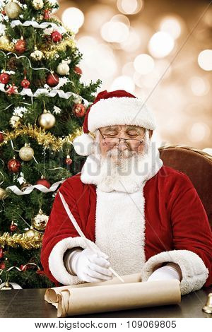 cheerful Santa Claus writing on scroll paper with quill