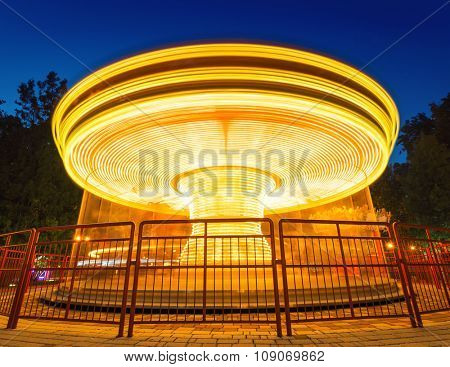 Fast merry-go-round lighting in the night park