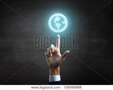 Businessman is indicating  a blue globe icon on black blackboard.