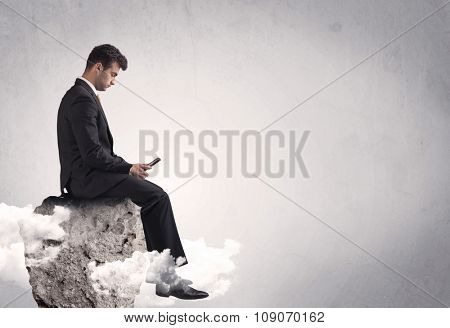 An elegant  smart businessman with laptop sitting in empty grey space on top of a cliff, between clouds concept