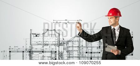 A young architect planning and drawing a family house layout with measurements, lines, numbers, angles