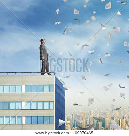 Businessman on the roof looking at falling documents