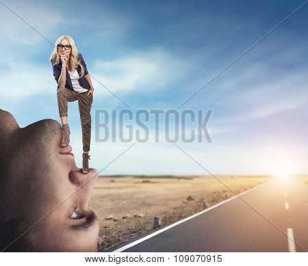 Young confident woman standing on the man's face