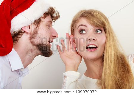 Man In Santa Hat Whispering To Woman Ear.