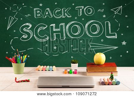 Back to school concepty with writing on blackboard and desk, apple, books, items