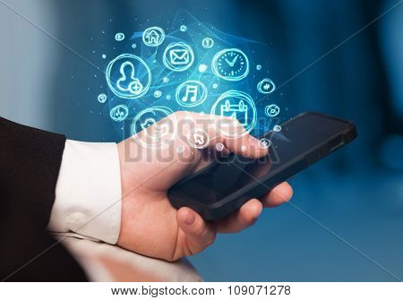 Hand holding smartphone with glowing mobile app choices